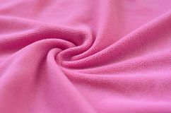 The blanket of furry pink fleece fabric. A background of light pink soft plush fleece material with a lot of relief fold. S Royalty Free Stock Photography