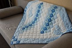 Blanket made manually from fabric slices 2996. Embroidered by dark blue and white patterns a scrappy blanket Stock Photo