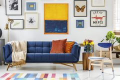 Blanket on navy blue settee in modern living room interior with. Gallery of posters. Real photo royalty free stock image