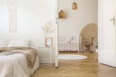 Blanket on white bed in bedroom interior with peacock chair next to child`s cradle. Real photo stock photography