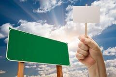 blankt grönt vägmärke för holdingmanaffisch arkivfoto
