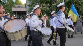 Blaskapelle auf Parade, junge Seeleute im weißen einheitlichen Spiel auf großen Trommeln und ukrainische Flagge an der Straße in  stock footage