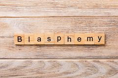 BLASPHEMY word written on wood block. BLASPHEMY text on wooden table for your desing, concept stock image