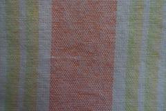 Blasse orange, gelbe und grüne vertikale Streifen auf weißem Gewebe Lizenzfreie Stockfotografie