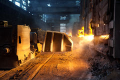 Blast furnace in factory. Glowing flames shooting out of an opening in a large industrial blast furnace royalty free stock images