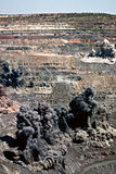 Blast in open cast mine. Excavators,trucks and heavy technics in open cast mine after blast among dust and smoke Royalty Free Stock Photo