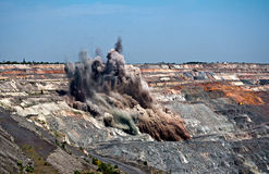 Blast in open cast mine. Excavators,trucks and heavy technics in open cast mine after blast among dust and smoke Royalty Free Stock Images