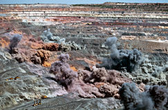 Blast in open cast mine. Excavators,trucks and heavy technics in open cast mine after blast among dust and smoke stock image