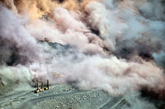 Blast in open cast mine. Excavators,trucks and heavy technics in open cast mine after blast among dust and smoke Stock Photography
