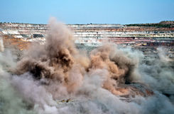 Blast in open cast mine. Excavators,trucks and heavy technics in open cast mine after blast among dust and smoke Stock Images