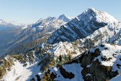Blasten av bergen som täckas med snö En man och en kvinna c Arkivfoton