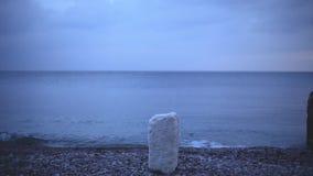Blaszanej puszki cel na kamieniu na plaży strzelający uderza cel cyna spada i chłopiec biega stawiać je na miejscu zbiory