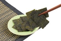 Blatt der getrockneten knusperigen Meerespflanze in den Essstäbchen und des Tellers lokalisiert auf weißem Hintergrund Stockbild
