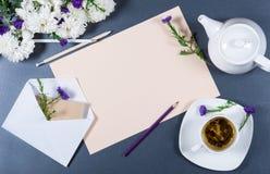 Blatt des beige Papiers, der frischen Chrysanthemen, der Bleistifte, des Umschlags mit Anmerkung und Blume, der weißen Tasse Tee  Stockbilder