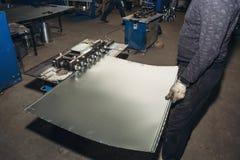 Blatt des Metalls in den Arbeitskrafthänden, Metallarbeitsausrüstungswerkzeuge auf industrieller Fabrik Stockbild