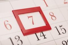 Blatt des Wandkalenders mit rotem Kennzeichen auf gestaltetem Datum 7 Stockbilder
