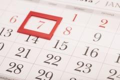 Blatt des Wandkalenders mit rotem Kennzeichen auf gestaltetem Datum 7 Stockfotos