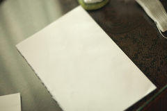 Blatt Papier liegend auf Tabelle unter warmem Sonnenunterganglicht Lizenzfreies Stockbild