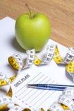 Blatt Papier mit Diätplan, Apfel, Stift und Maßband Lizenzfreie Stockfotos