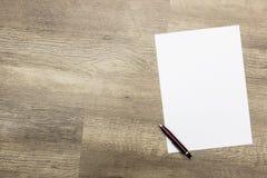 Blatt Papier und Stift auf Holztisch Lizenzfreies Stockbild