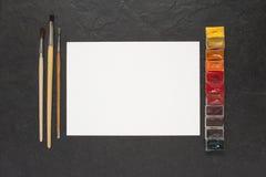 Blatt Papier und Wasserfarben auf dem Tisch Lizenzfreie Stockfotografie