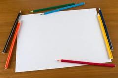 Blatt- und Farbenbleistifte des unbelegten Papiers auf Tabelle Lizenzfreie Stockbilder