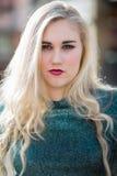 Blauäugige blonde Jugendliche mit Lippenstift und grünem T-Shirt Lizenzfreie Stockbilder