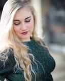 Blauäugige blonde Jugendliche mit Lippenstift und grünem T-Shirt Stockfoto