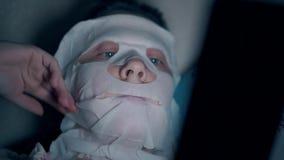 Blau?ugige Person repariert wei?e Blattmaske auf Backen und Kinn stock video