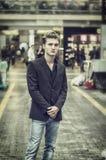 Blauäugiger, blonder junger Mann, der innere Bahnstation steht Lizenzfreies Stockfoto