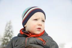 Blauäugiger kleiner Junge in einer Winterlandschaft lizenzfreies stockfoto