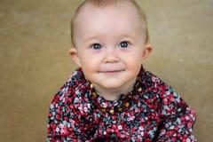 Blauäugiges Baby im Blumenhemdlächeln Stockfotos
