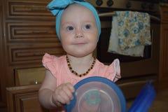 Blauäugiges Baby mit tupperware Stockfoto