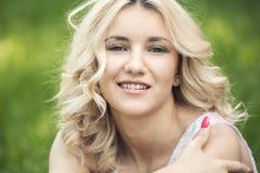 Blauäugiges blondes Lügen auf dem Gras Stockbilder