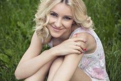 Blauäugiges blondes Lügen auf dem Gras Stockfoto