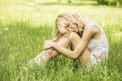 Blauäugiges blondes Lügen auf dem Gras Stockfotos