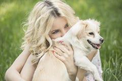 Blauäugiges blondes Lügen auf dem Gras Stockfotografie