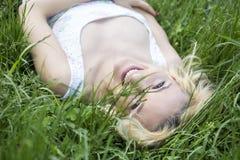 Blauäugiges blondes Lügen auf dem Gras Stockbild