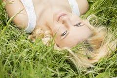 Blauäugiges blondes Lügen auf dem Gras Lizenzfreies Stockbild