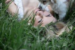 Blauäugiges blondes Lügen auf dem Gras Lizenzfreie Stockbilder