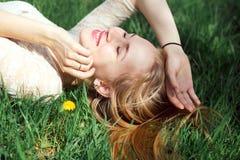 Blauäugiges blondes Lügen auf dem Gras mit Löwenzahn Nettes junges Girfriend reizendes Lachen in warmem Sunny Day Lizenzfreie Stockfotos