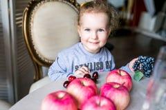 Blauäugiges nettes Mädchen, das an einem Tisch mit Äpfeln, Kirschen, Trauben und dem Lächeln sitzt stockfoto