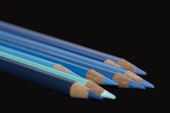 8 Blau farbige Bleistifte - schwarzer Hintergrund Stockfotografie
