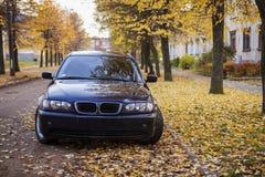 Blau farbiges Auto in der Herbststraße Stockfotos