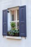 Blau Fensterläden geschlossene Fenster-und Blumenkasten-Blumen Lizenzfreie Stockfotos