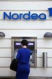 Blau gekleidete Frau machen ein withdravel von Nordea-Kasse stockfotografie