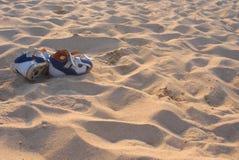 Blau-orange Sandalen auf einem sandigen Ozeanstrand lizenzfreies stockbild