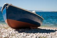 Blau-rotes Boot auf dem Strand Stockbild