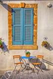 Blau schließt Fenster und schöne kleine Stühle und eine Tabelle auf s Fensterläden Stockfoto