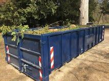 Blau speichert den Behälter aus, der mit Gartenabfälleniederlassungen, Blätter gefüllt wird lizenzfreie stockbilder